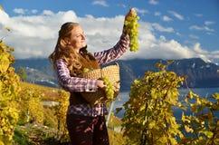 Flicka med en korg som är full av druvor royaltyfri foto