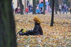 Flicka med en krans av gula lönnlöv på hennes huvud royaltyfria foton