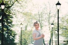 Flicka med en kvist av körsbärsröda blomningar i hennes händer Hon tycker om th royaltyfri fotografi