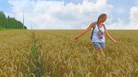 Flicka med en lie i fältet med öron i sommar Royaltyfri Fotografi