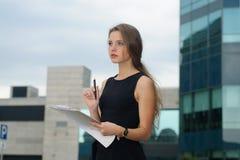 Flicka med en mapp för legitimationshandlingar i hennes händer Arkivfoto
