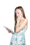 Flicka med en minnestavla i förvånade händer royaltyfri fotografi