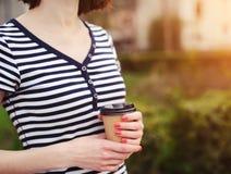 Flicka med en pappers- kopp Arkivbild