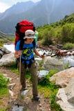 Flicka med en ryggsäck längs floden Arkivfoto