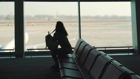 Flicka med en ryggsäck som väntar på ett flyg stock video