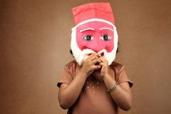 Flicka med en santa maskering Arkivbild