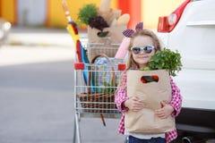 Flicka med en shoppingvagn mycket av livsmedel nära bilen arkivbild