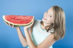 Flicka med en skiva av den mogna vattenmelon Arkivfoto