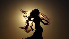 Flicka med en skyla i henne händer som dansar magdans på stranden silhouette långsam rörelse lager videofilmer