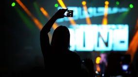 Flicka med en Smartphone på en vaggakonsert lager videofilmer