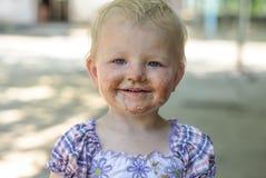 Flicka med en smutsig framsida Fotografering för Bildbyråer