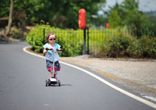 Flicka med en sparkcykel Arkivfoton