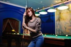 Flicka med en stickreplik i henne händer som spelar biljard Fotografering för Bildbyråer