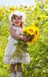 Flicka med en stor bukett av solrosor Fotografering för Bildbyråer
