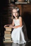 Flicka med en stor bunt av böcker Royaltyfria Bilder
