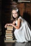 Flicka med en stor bunt av böcker Royaltyfri Bild
