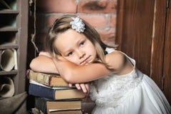 Flicka med en stor bunt av böcker Arkivbild
