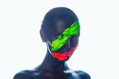 Flicka med en svart målarfärg på framsidan grön red arkivfoton