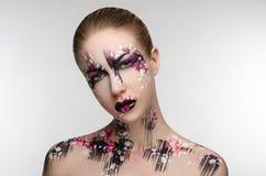 Flicka med en svart- och rosa färgmakeup royaltyfria bilder