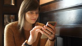 Flicka med en telefon i händer lager videofilmer