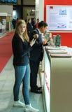 Flicka med en telefon och en man av det asiatiska utseendet på exhiben Royaltyfri Foto