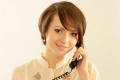 Flicka med en telefon på en ljus bakgrund Arkivfoton