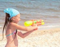 Flicka med en vattenpistol på stranden Royaltyfria Foton