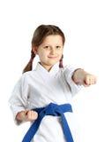 Flicka med ett blått bälte takten en stansmaskinhand på en vit bakgrund Arkivbild