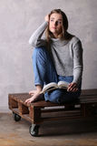 Flicka med ett boksammanträde på träbräde Grå färgbakgrund Royaltyfri Foto