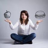 Flicka med ett dilemma om mat Arkivbild