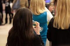 Flicka med ett exponeringsglas av champagne på partiet dricka flicka för champagne isolated rear view white Royaltyfri Fotografi