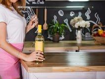 Flicka med ett exponeringsglas och en flaska av vitt vin royaltyfria foton