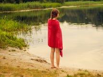 Flicka med ett handdukanseende på flodbanken Fotografering för Bildbyråer