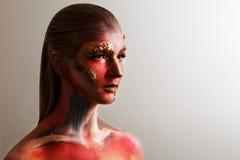 Flicka med ett intressant smink som ser upp Kroppkonst, framsidakonst makeup för halloween, grå bakgrund Royaltyfria Foton