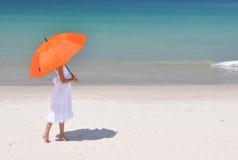 Flicka med ett paraply på den sandiga stranden Royaltyfri Foto