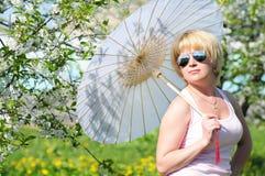 Flicka med ett paraply i den frodiga trädgården Arkivbild