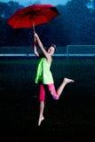 Flicka med ett paraply i regnet Arkivbilder