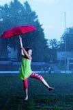 Flicka med ett paraply i regnet Arkivbild