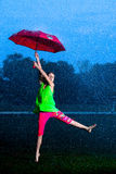 Flicka med ett paraply i regnet Fotografering för Bildbyråer