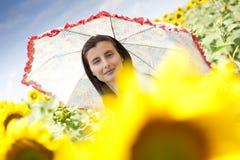 Flicka med ett paraply i solrosfält Arkivbilder