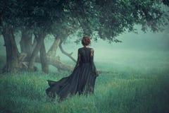 Flicka med ett rött hår som promenerar från den mörka skogen, bärande lång svart klänning med släpet som vinkar i vinden royaltyfria foton