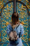 Flicka med ett ryggsäckanseende nära en härlig dörr royaltyfri bild