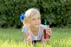 Flicka med exponeringsglas av fruktsaft royaltyfri bild