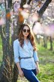 Flicka med exponeringsglas i träden royaltyfri foto