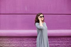 Flicka med exponeringsglas på en purpurfärgad vägg royaltyfria bilder
