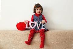 Flicka med förälskelsetecknet och röd flott hjärta Royaltyfri Foto