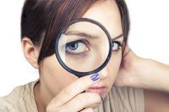 Flicka med förstoringsglaset över hennes framsida Arkivbild