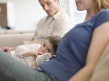 Flicka med fadern And Mother Relaxing hemma Arkivbild