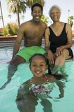 Flicka (5-6) med fadern och farmodern på simbassängståenden. arkivfoto
