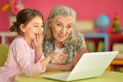 Flicka med farmodern som använder bärbara datorn Royaltyfri Fotografi